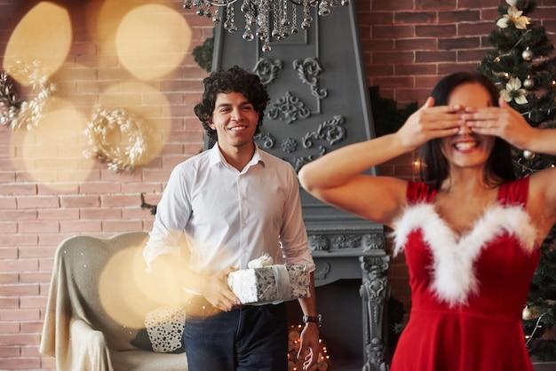 Chodzenie do dziewczyny i uśmiechanie się. kobieta w czerwonej sukience otrzyma teraz prezent świąteczny od chłopaka.