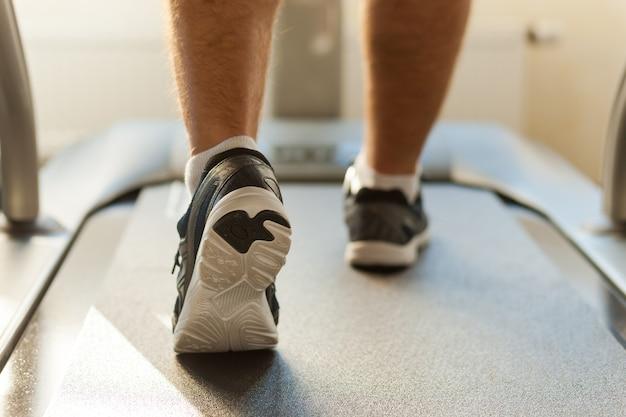 Chodzenie na bieżni. zbliżenie: mężczyzna chodzący na bieżni w klubie sportowym