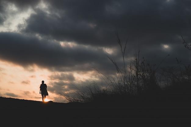 Chodzić samotnie na wzgórzu z zmierzchem w tle