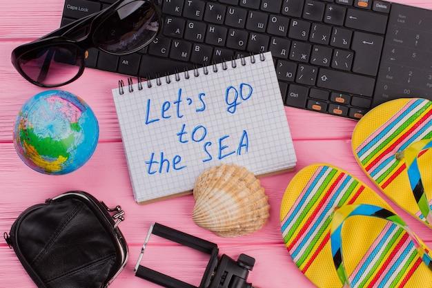 Chodźmy do morskiego notatnika z kobiecym podróżnikiem akcesoria okulary portfel i klapki na różowym tle blatu stołu. globus i czarna klawiatura.