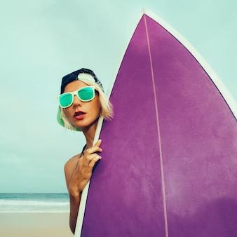 Chodźmy posurfować. dziewczyna z deską surfingową na plaży