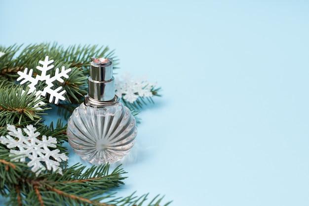 Choinka i butelka perfum z bliska na niebieskim, copycopyspace