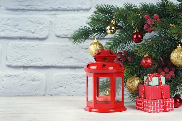 Choinka i ozdobna latarnia ze świeczką. czerwona latarnia retro, pudełko upominkowe i piłki