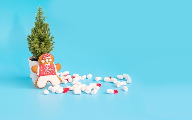 Choinka i piernikowy mężczyzna na błękitnym tle. kreatywna koncepcja nowego roku i świąt bożego narodzenia