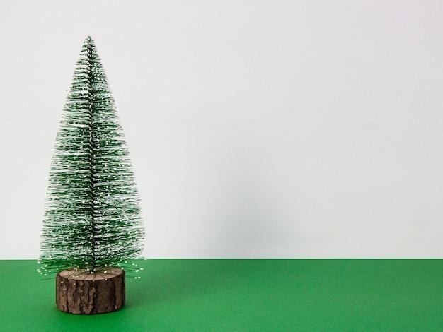 Choinka na białym tle na zielonej powierzchni z białym tłem i kopia przestrzeń, kartki świąteczne, widok z przodu