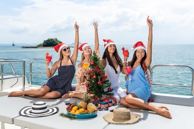 Choinka na jachcie. cztery dziewczyny świętują boże narodzenie na jachcie