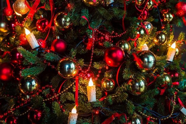 Choinka noworoczna ozdobiona złotymi i czerwonymi zabawkami