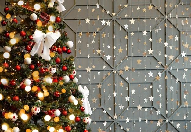 Choinka ozdobiona błyszczącymi kulkami i kokardkami na szarej ścianie z migoczącymi światłami