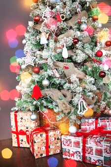 Choinka ozdobiona błyszczącymi kulkami i prezentami przewiązanymi czerwonymi wstążkami, na tle bokeh