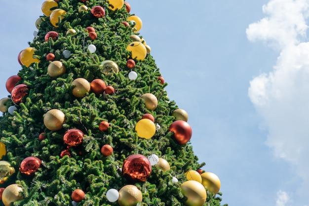 Choinka ozdobiona czerwonymi, żółtymi i srebrnymi ornamentami z jasnym tle nieba.
