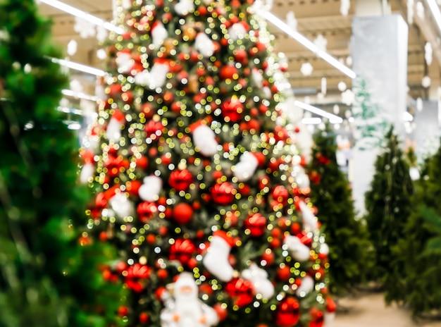 Choinka ozdobiona na boże narodzenie wśród nieozdabionych jodeł w sklepie. jarmark bożonarodzeniowy w dużym sklepie. boże narodzenie kartkę z życzeniami.