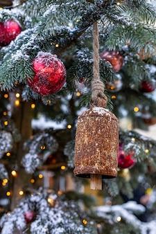 Choinka ozdobiona zabytkowymi dzwonami i piłkami na niewyraźne musujące streszczenie