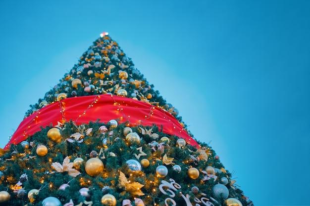 Choinka pod błękitnym niebem. widok z dołu na świątecznie udekorowane drzewo. noworoczne ferie zimowe