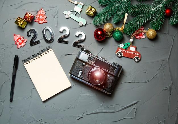 Choinka rozgałęzia się aparatem fotograficznym i notatnikiem na tekst na szarym betonowym tle