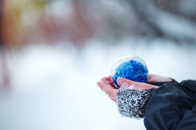 Choinka w rękach dziecka. okrągła niebieska piłka boże narodzenie na tle śniegu.