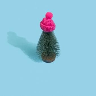 Choinka w różowej czapce zimowej na pastelowym niebieskim tle