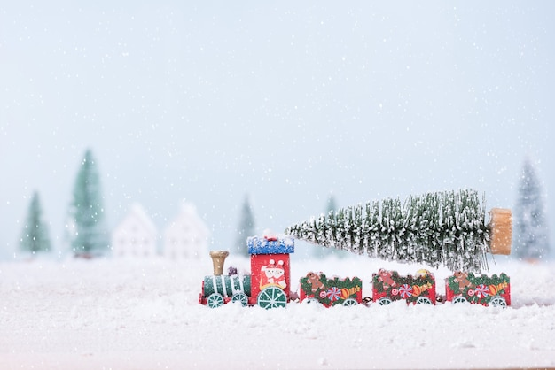 Choinka w zabawkowym pociągu biegła przez śnieg na tle naturalnego krajobrazu.