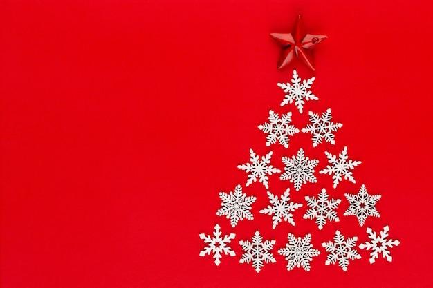 Choinka wykonana z białych płatków śniegu na czerwonym tle z pustym miejscem na tekst. nowy rok i pocztówka świąteczna.