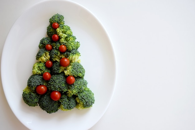 Choinka wykonana z brokułów i małych pomidorów na białym talerzu na białym tle. zdrowa żywność ekologiczna.