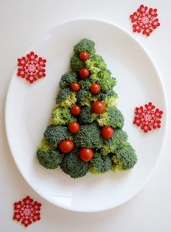 Choinka wykonana z brokułów i małych pomidorów z czerwonymi płatkami śniegu na białym talerzu na białym tle.