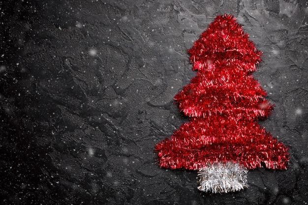 Choinka wykonana z czerwonego świecidełka jako ozdoba świąteczna wianek