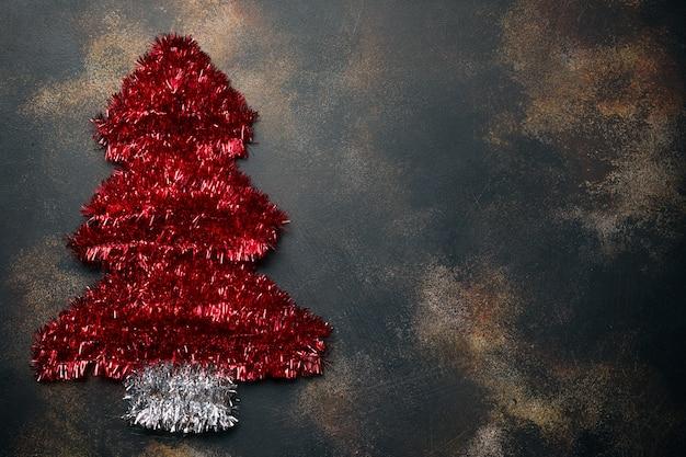 Choinka wykonana z czerwonego świecidełka. ozdoba choinkowa na kamieniu.