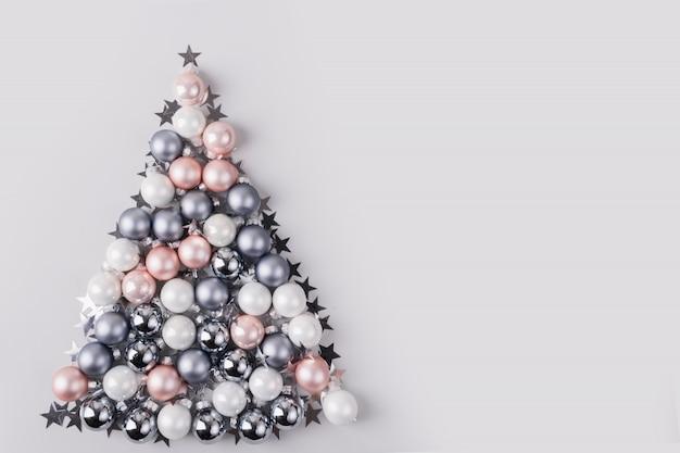 Choinka wykonana z gwiazd, srebrnych kulek na szarym tle. kompozycja świąteczna. leżał płasko, widok z góry, miejsce. karta z pozdrowieniami świątecznymi.