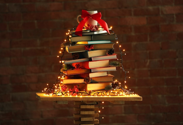 Choinka wykonana z książek na stole na tle ceglanego muru
