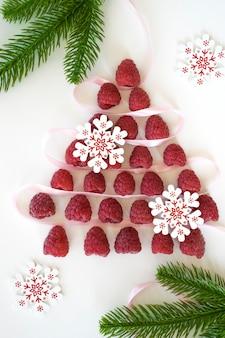 Choinka wykonana z malin, białych z czerwonymi płatkami śniegu i gałęziami jodły