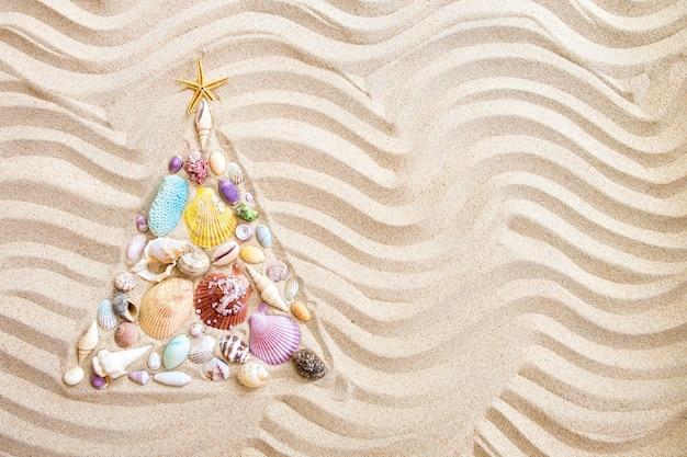Choinka wykonana z muszli i koralowców na piaszczystej plaży, płaskie tło