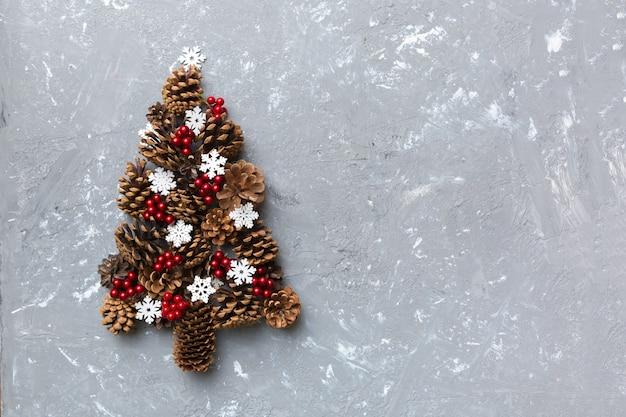 Choinka wykonana z naturalnych szyszek na kolorowym tle, widok z góry. noworoczna minimalna koncepcja z miejscem na kopię