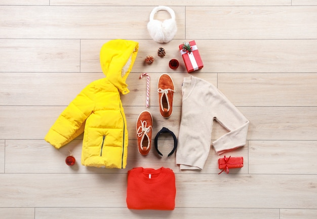 Choinka wykonana z zimowych ubrań i akcesoriów na drewnianym stole, widok z góry