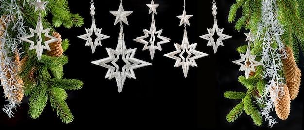 Choinka z błyszczącymi srebrnymi gwiazdami na czarnym tle. świąteczne dekoracje