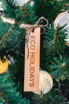 Choinka z drewnianą zabawką i tekstem wakacje ekologiczne