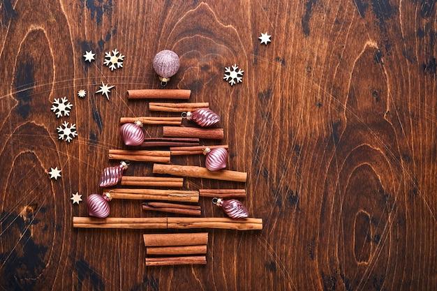 Choinka z jodły w kształcie cynamonu i anyżu z czerwonymi i zielonymi bombkami na tle drewna na świąteczne pozdrowienia. widok z góry z miejsca na kopię.