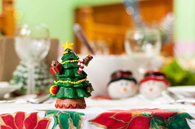 Choinka z kilkoma spiczastymi wykałaczkami w kształcie świątecznych przedmiotów na stole ze świątecznym obiadem