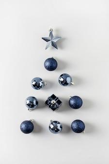 Choinka z klasycznymi niebieskimi kulkami i gwiazdkami w pastelowej szarości. ścieśniać. karta z pozdrowieniami świątecznymi. widok z góry.
