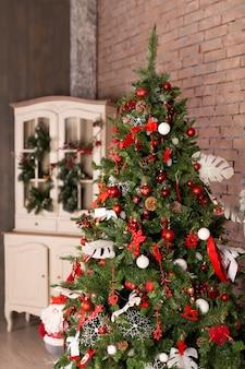 Choinka z kolorowymi piłkami i prezentów pudełkami nad ściana z cegieł. boże narodzenie nowy rok koncepcja. dekoracja.