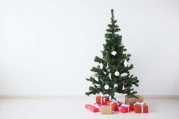 Choinka z kulkami i pudełka na prezenty na białej ścianie z miejsca na kopię