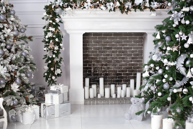 Choinka z kulkami, kominkiem ze świecami i prezentami w salonie. świąteczne wnętrze pokoju utrzymane jest w białej kolorystyce, ozdobione choinką i dekoracyjnymi elementami kominka