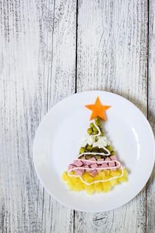 Choinka z oliwki sałatkowej w talerzu na białym drewnianym stole. widok z góry z miejscem na kopię.