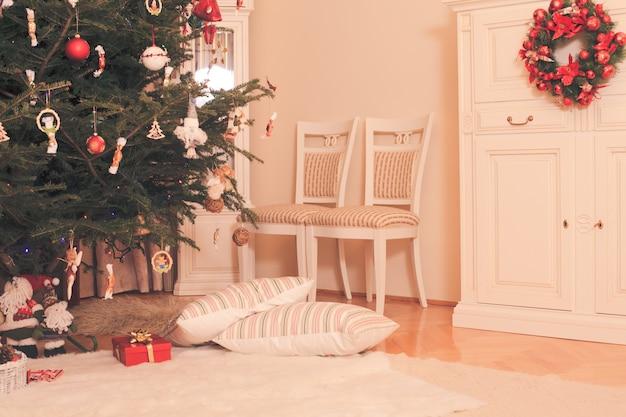 Choinka z prezentami pod mikołajem i dwiema poduszkami leżącymi obok