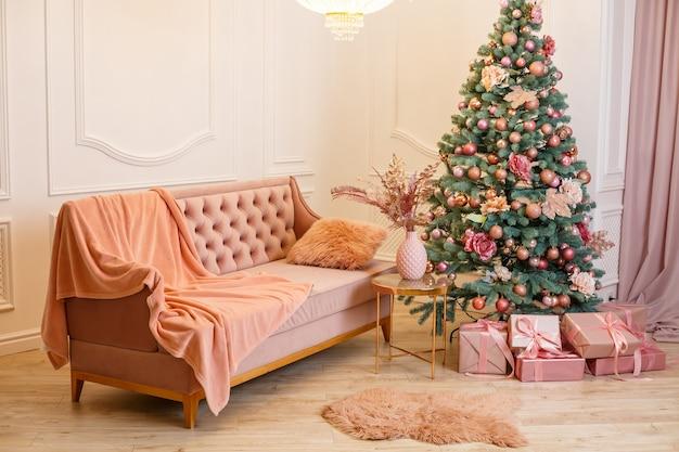 Choinka z różowymi prezentami w białym pokoju bożonarodzeniowym. ładnie urządzony domek z różowymi zabawkami ozdobiony choinką i prezentami na boże narodzenie.