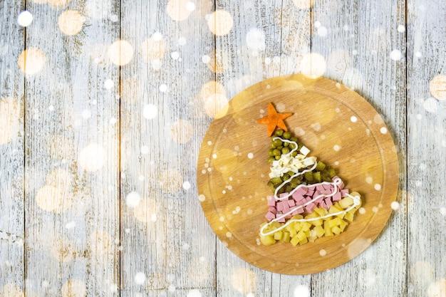 Choinka z sałatki olivier na desce do krojenia na białym drewnianym stole. widok z góry z miejscem na kopię. stonowany bokeh i śnieg