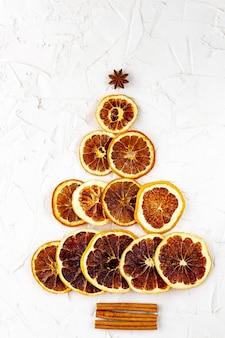 Choinka z suszonych cytrusów i cynamonu, anyżu na białym tle. pomarańcze, cytryny, grejpfruty w kształcie jodły