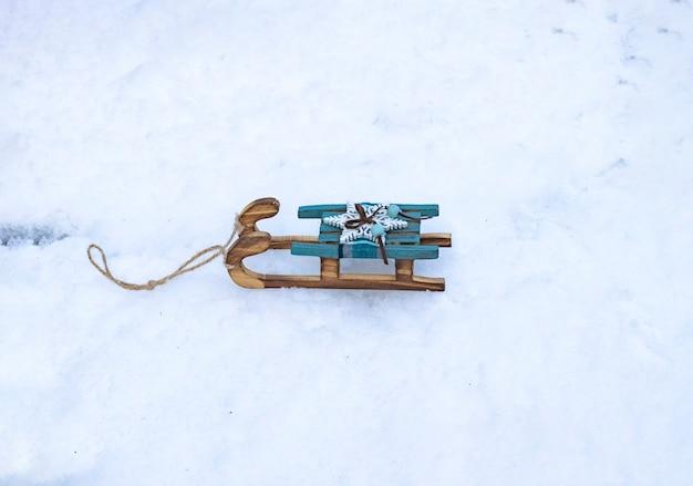 Choinka zabawka małe drewniane sanki retro na śniegu w zimie