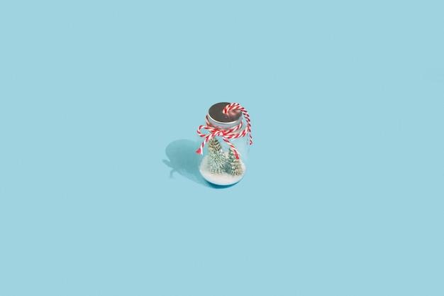 Choinka ze śniegiem w szklanym słoju na niebieskim tle zimy