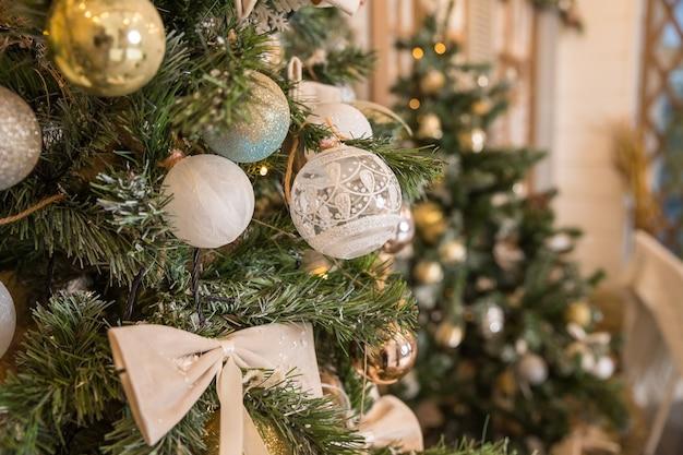 Choinki ozdobionej perłą, srebrem, kryształem, złotymi kulkami oraz zabawkami z białą ścianą.
