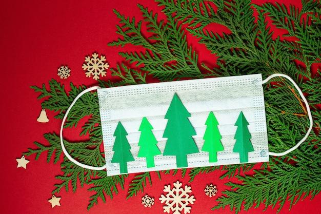 Choinki wycięte z papieru z jednorazową maseczką medyczną i zielone gałęzie jodły na czerwonym tle. kartka do cięcia papieru choinkowego. maska na twarz ze świątecznymi dekoracjami. mieszkanie leżeć