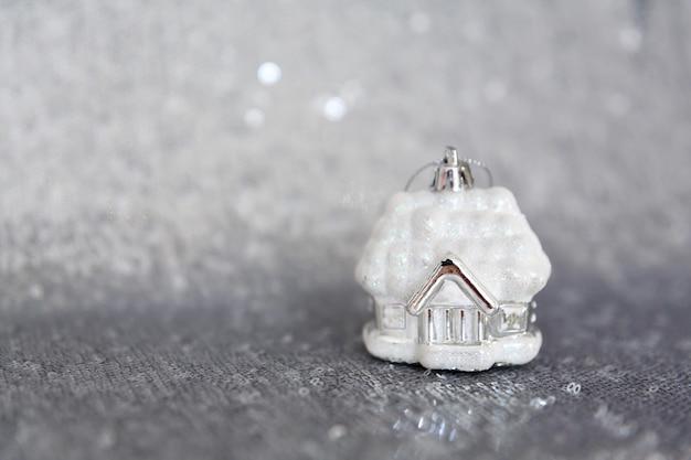 Choinkowy domek w śniegu, stoi na materiale z błyszczącymi cekinami